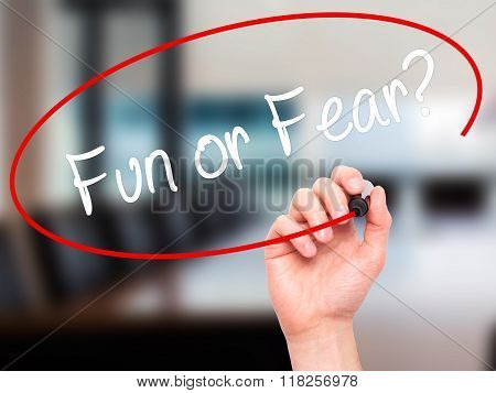 Man Hand Writing Fun Or Fear?  With Black Marker On Visual Screen