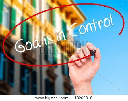 Man Hand Writing God Is In Control With Black Marker On Visual Screen