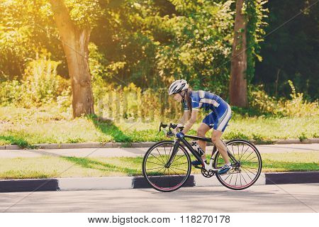 Female sportsman cyclist riding racing bicycle. Woman cycling on countryside summer sunny road or highway. Training for triathlon or cycling competition. poster