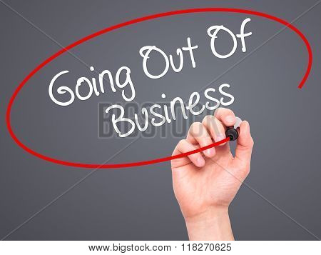Man Hand Writing Going Out Of Business With Black Marker On Visual Screen