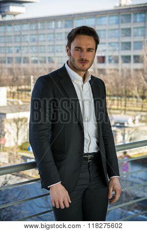 Handsome man outside against hand-railing