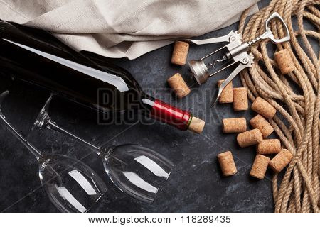 Wine, glasses and corkscrew over stone background. Top view