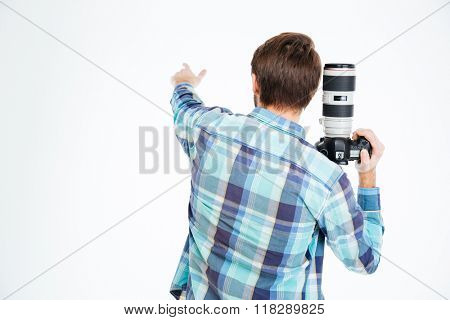 Back view portrait of a male photographer holding photo camera and pointing on something isolated on a white background