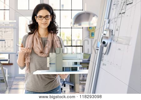Female casual caucasian architect designer with building model holding in hand, standing, smiling, looking at camera. Bright office.
