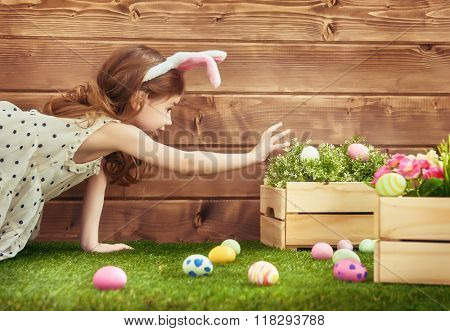 Happy Easter! Cute little child girl wearing bunny ears on Easter day. Girl hunts for Easter eggs on the lawn near the house.