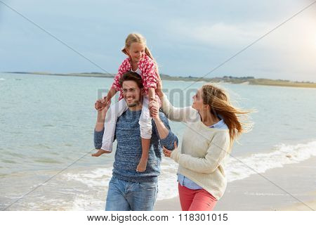 Family On Beach Vacation Walking By Sea