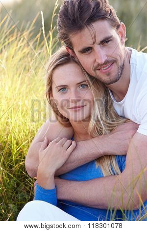 Portrait Of Couple Sitting In Sand Dunes