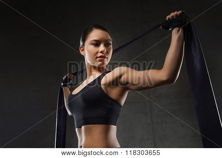 fitness, sport, training, people and lifestyle concept - woman doing exercises with expander or resistance band in gym