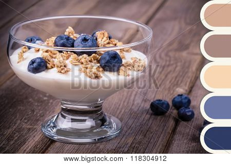 Yogurt with blueberries and granola over old wood background. In a colour palette with complimentary colour swatches.