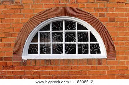 Exterior of a brick building with an arched window.