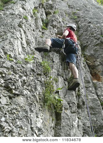 Young Caucasian male climbing on a lime rock wall using safety ropes. poster