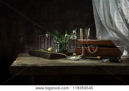 Still Life With Jewelery Box, Old Book And Snowdrop Flowers On A Rustic Wooden Table Against A Dark