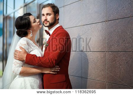 Bride and groom, romantic wedding couple in a passionate outburst, near walls of building.
