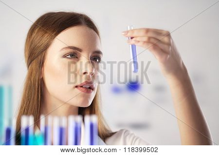 Scientist working in the lab. Chemist looking at a glass vile