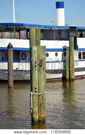 Pier pilings by a tour boat