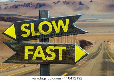 Slow - Fast signpost in a desert background