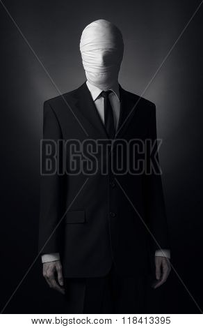 Internet meme and terrible character Halloween theme: very tall burly man with long arms in a suit with bandaged face fabric an unknown killer in the suit The Slender Man Secret legend of the city in studio poster
