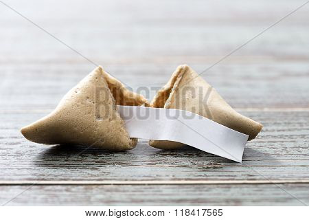 Fortune cookie with blank slip isolated on table.