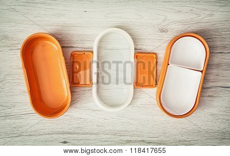 Orange Folding Plastic Food Box On The Wooden Background