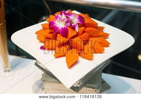 Bite sized papaya fruit on white plate over white background