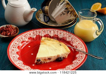 Homemade Cottage Cheese Cheesecake On Red Plate With Lemon Curd, Tea And Goji Berries