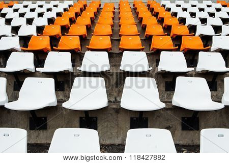 Empty orange and white seats at stadium.