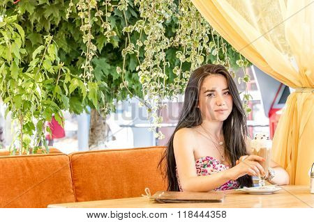 outdoor portrait of young woman waiting for somebody in street cafe
