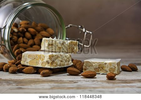 Nougat In Front Of A Glass Jar With Almonds On A Rustic Wooden Table, Copy Space, Close U