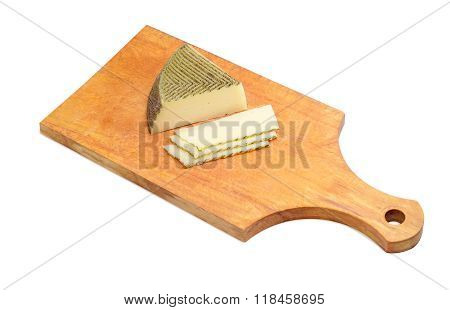 Partly Sliced Spanish Cheese On Wooden Kitchen Cutting Board