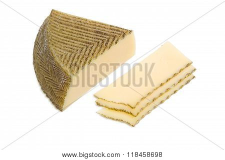 Piece And Several Slices Of Spanish Cheese On Light Background
