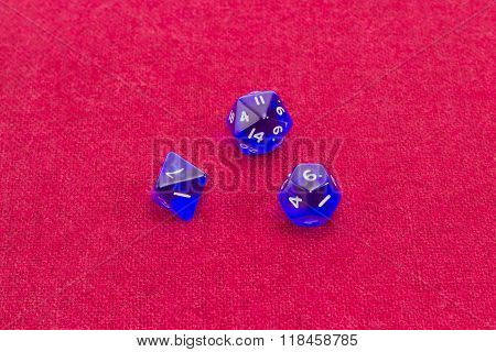 Three Polyhedral Role Playing Dice On Table With Red Cloth