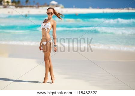 The young attractive woman in bikini on a beach