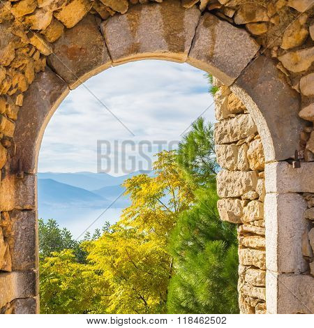 Beautiful landscape at Nafplio in Greece through the old arched stoney doorway of Palamidi castle.