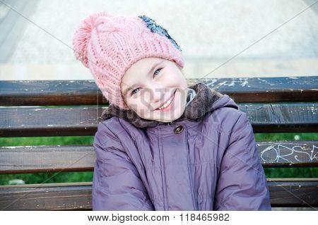 Happy girl-schooler sitting on bench in city park.