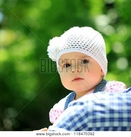 Baby girl cute hazel-eyed kid tiny little child wearing white flower beanie hat held by father portrait outdoor on sunny summer day on blurred green background square picture
