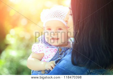 Mother kissing and holding small daughter baby girl cute hazel-eyed kid tiny little child wearing white flower beanie hat outdoor sun spot summer day on blurred green background horizontal picture