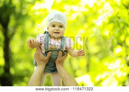 Baby girl smiling hazel-eyed kid tiny little child wearing white flower beanie hat lifted in air high by hands portrait outdoor on summer day on blurred sunny background horizontal picture