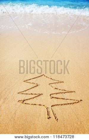 Christmas tree drawn in sand at the beach