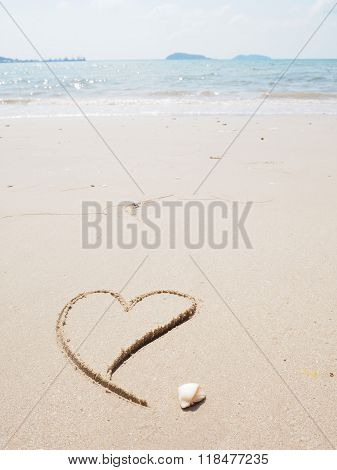 Heart-shape drawing left-side on the sandy beach with sea background