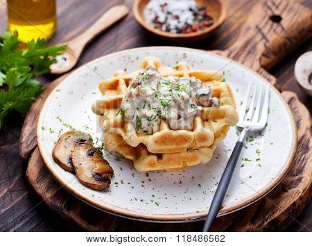 Savory waffles with corn and mushroom creamy sauce on a wooden background