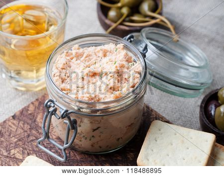 Smoked salmon and soft cheese spread, mousse, pate in a jar with crackers and capers on a wooden bac