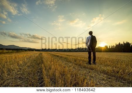 Businessman In Elegant Suit With His Jacket Hanging Over His Shoulder Standing In Mown Wheat Field