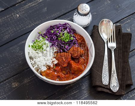 Bowl Of Stewed Meat, Rice And Red Cabbage. Tasty Healthy Food. On A Dark Wooden Background