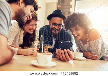 Friends Looking At Smart Phone While Sitting In Cafe