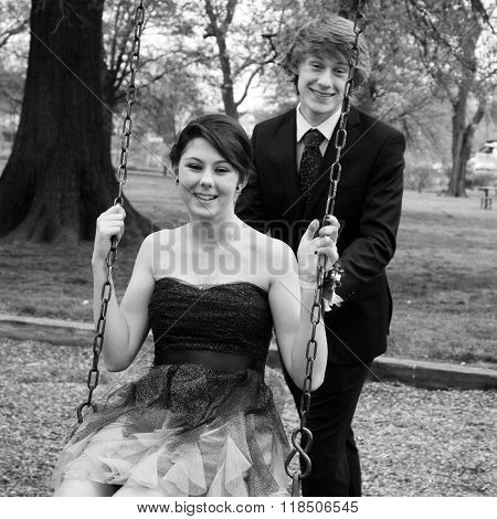 Black and white photo of attractive teen couple pose outdoors on swing set for prom.
