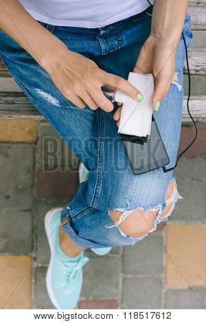 Girl In Torn Jeans Sitting On A Bench And Cleans Mobile Phone Antibacterial Spray