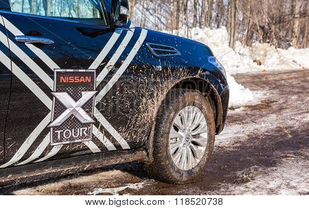 Front Part Of The Car Nissan Patrol With Dirty Wheel On The Rural Road In Winter Day
