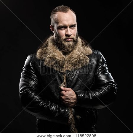 Brutal handsome glum unshaven man with long beard and moustache in black fur coat with collar poster
