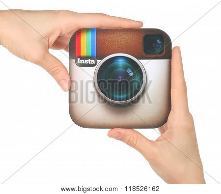 Hands hold Instagram logo printed on paper on white background
