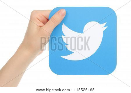 Hand holds twitter icon printed on paper